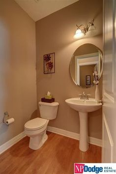 Traditional Powder Room with Frameless Oval Mirror, specialty door, High ceiling, Powder room, Hardwood floors, Pedestal Sink