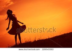Young beautiful woman's silhouette at sunset by Linda Moon, via ShutterStock