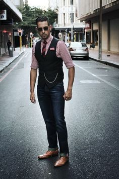 Go for a chic style in red gingham shirt, red and navy striped tie, navy waistcoat, blue jeans, tan brogues