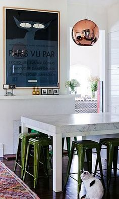12 Kitchens & Dining Rooms Made Cozy With Kilims: Tom Dixon's copper pendant is just the right touch for picking up the earthy tones of the kilim in this Melbourne, Australia dining space. The green tolix stools are an unexpected touch.