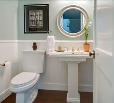 Powder room with blue walls, wainscoating, and pedestal sink