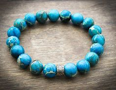 Blue Bracelet Mens. The bright turquoise blue of the imperial jasper beads that make up this handmade men or unisex stretch bracelet are simply stunning! They are strung on high quality elastic cord to provide a secure, yet stretchy fit. A single silver plated bead provides the perfect focal point. Length: Bracelet will be made to fit. Finding Your Perfect Bracelet Size: While making a fist, measure the size of your wrist with a tailors tape or piece of string. Add a quarter of an inch to…
