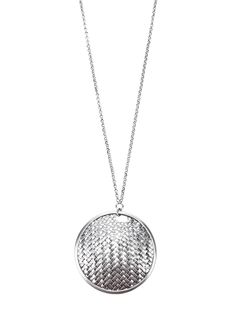 Metallic silver necklace from Les Perles De Noa featuring a long silver chain and a woven disc design silver pendent.