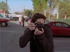 """Nikon F4 in Scrubs In Season 3 Episode 18, """"His Story II"""", JD nonchalantly whips out a Nikon F4 to take a photo of his friend, Turk. The episode first aired in April 2004.  Though it's hard to tell which exact model fo F4 the camera is in this screen-grab, considering Nikon ceased production of the F4 in 1997, this was already an old camera at the time of filming. Nice touch, I think."""