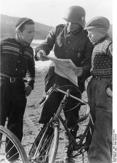 A german soldier reads a news paper with two norwegian children, Norway, 1940