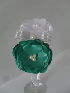 Tiara encapada com fita de cetim branco. Flor em cetim branco e verde. Acabamento em pérolas e laço. R$ 17,00