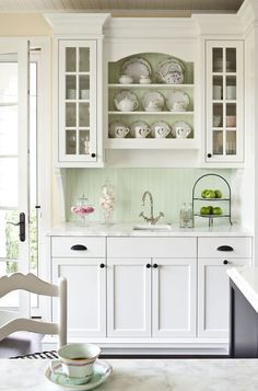 If you just can't imagine anything except pristine white kitchen cabinets, but you are drawn to a little mint, feature it in a small area, such as a new tile backsplash.