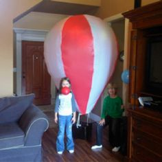 DIY: Hot air balloon made with plastic  disposable tablecloths, double-sided tape, and a coat hanger. Needs about 250+ helium balloons to inflate or a hot hair dryer blowing at it from underneath.