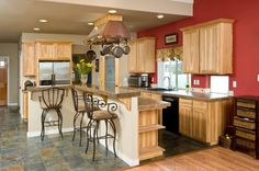 An eclectic kitchen with light wood cabinets without pulls and tile floors in a dusky blue-gray mottled with bronze-beige. A vent hood doubles as a pot rack above the two-tier eat-in kitchen island.
