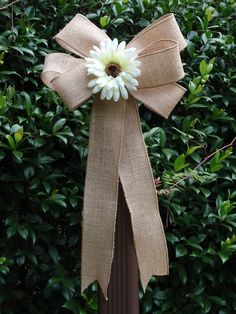 Idea for decorating the fence behind us during the ceremony... except I would use lace over the burlap and a different color gerber daisy...