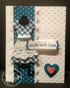 The dress is made using Stampin' Up's Dress Form framelits. The apron is one of their doilies. Also used are the polka dot embossing folder, Hearts a Flutter Framelits for the larger heart and the small heart punch for the pink heart, modern label punch, and the eyelet border punch (retired).