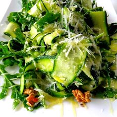 Thinly sliced zucchini in a bed of baby arugula, lemon zest, Parmesan shavings, and walnuts.