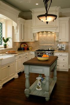 Window and stove hood arches are wonderful. Love that the butcher block/island is a different color from the cabinets.