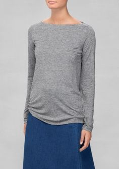 Classically elegant and feminine, this light wool top has a narrow bateau neck and a clean, straight fit.