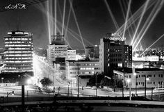 Looking south on Vine Street as seen from the Hollywood Freeway, ca. 1950s. Spotlights illuminate the sky wih beams of light. From left to right are the: Capitol Records Building, The Broadway-Hollywood Building, and the Hotel Knickerbocker. Source: LAPL