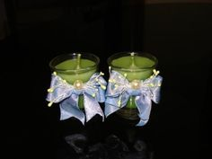 Hand poured green candles in shot glasses decorated with blue ribbons