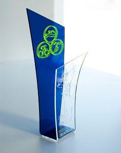 Statuetka sportowa o ciekawym kształcie na triathlon.Wykonana z pleksi bezbarwnej z wygrawerowaną łuczniczką,pleksi transparentnej niebieskiej,pleksi fluorescencyjnej zielonej.