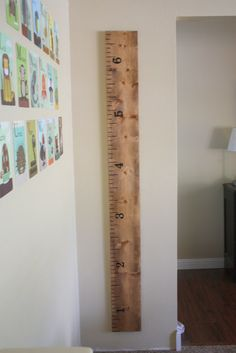 """my """"ruler"""", I sprayed the entire board with a clear coat to protect my work. This still allows me to measure my son's height and mark on it, but gives it a finished look.  To hang it, I simply attached a sawtooth pi"""