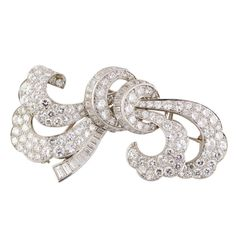 Beautiful ribbon-like double clip brooch by J.E. Caldwell & Co., circa 1940s/50s. It features approx. 15.00cts of round and baguette cut diamonds on a platinum setting. Hallmarks: J.E. Caldwell, reference numbers.