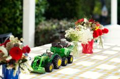 Love the mixture of pretty flower arrangements and a tractor-filled with party snacks as centerpieces at this Barnyard Birthday Party!