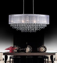 A stunning white shade pendent chandelier trimmed with spotless clear crystal to add an elegant touch to every home.