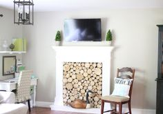 Note small office space Behr Castle Path paint with faux fireplace with stacked birch wood logs and tv mounted over fireplace with preserved boxwoods www.goldenboys...