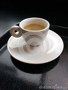 An empty espresso cup sits on a black tray against a black background. However, though empty, brown and tan layers of coffee foam remain around the inside of the vessel.