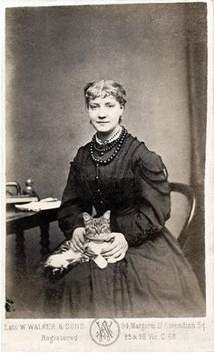 """Calm woman with serious cat. """"Late 1860's. Pencil notation on back: """"Nelly Moore""""."""