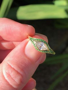 For Sale on - A singular Cleopatra's eye cut diamond (E/VS- ct) with a tsavorite pavé. An engagement truly like no other, this diamond is absolutely fascinating.