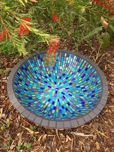 Rebecca Naylor Mosaics This bird bath bowl is made using glass and porcelain tiles. The iridescent tiles shine in the sun, sparkling through the water.  Measuring 47cms x 12cms on a terracotta base.