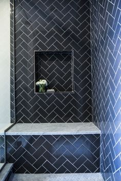 Contemporary shower features navy herringbone tiles accented with a navy tiled niche over a carrera marble shower bench.