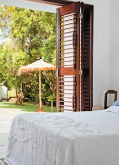 A porta do quarto também tem abertura para a área externa. No quarto, o jogo de cama de algodão (Trousseau) vai bem no calor.