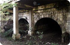Αστικό Σημάδι #45 : Αρδηττού και Καλλιρόης, Μετς  Εγκιβωτισμένη κάτω από το σύγχρονο δρόμο, η τρίτοξη γέφυρα του 19ου αιώνα είναι ακόμα ορατή από το τελευταίο σημείο που η κοίτη του Ιλισσού ποταμού παραμένει ακόμα ακάλυπτη.