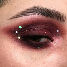 Deep burgundy eye makeup look featuring stars and glitter. Arty, editorial makeup.