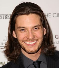 Long dark straight men's hairstyle with off center part and razored ends