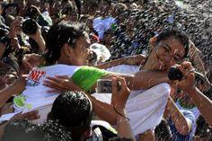 """Seorang gadis Bali (kanan) berusaha menghindar dari ciuman seorang pria saat festival keagamaan """"Omed Omedan"""" di Bali, Indonesia."""