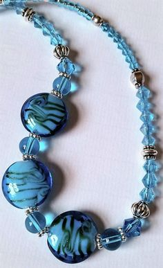This delightfully unique, eye-catching turquoise blue glass beaded necklace is sure to please! Created with aqua glass crystals and silver plated accents beads, it features three large blue glass disk
