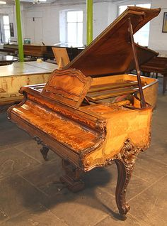 A Rococo Style, Erard Grand Piano For Sale with a Quarter Veneered, French Walnut Case. Cabinet Features Ornately Carved Legs and Cheeks. Beautifully Fine Inlay Adorns All Sides of the Cabinet in a Scrolling Floral Design. A Stunning Example of a Rococo Style Piano at Besbrode Pianos .