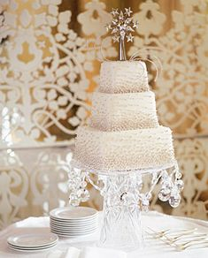 Tall cake stand-- made from a vase?Three-tier buttercream cake ornately detailed with silver sugar dragées, by Tomas Paulina and Lidiya Zdrok for     Twenty Four Fifth Avenue. Crystal and silver cake topper, by     Swarovski.