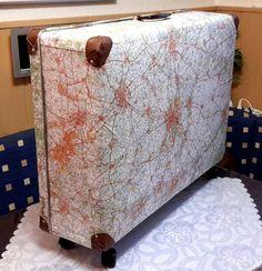 Een oude koffer beplakt met oude wegenkaarten. Hoeken van restjes leer en wieltjes eronder gezet.