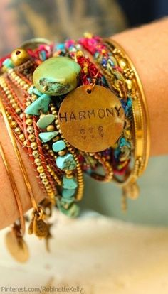 Charms on multiple colorful bracelets on gold and bronze metals turquoise agate coral