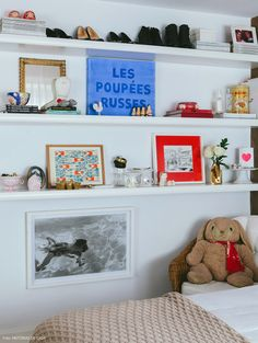 As prateleiras brancas instaladas nesse quarto servem para expor quadros e objetos.