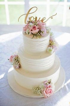 White pink and gold wedding cake idea - three-tier white wedding cake with pink roses gold LOVE modern calligraphy cake topper {Willow Noavi Photography}