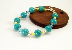 A bright fun bracelet of turquoise (dyed) Riverstone gemstones with little yellow luster glass beads to accent. I added a few silver elements and to close a small silver toggle clasp..Brighten any Fall or Winter darker outfit with a touch of color...Made and Ready to ship..* Total length including clasp is 8 3/4 inches..Fits an average sized wrist loosely and great for a larger wrist as well..♥  Matching Earrings are available as pictured in photo, find them in this section of my shop-   ...