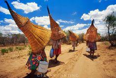Mbukushu women carrying fishing baskets, Okavango Delta, Botswana ©Frans Lanting