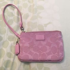 "Coach Wristlet USED. Pink ""C"" logo Wristlet. Signs of wear on the inside and out. Most likely can be cleaned with a damp cloth. Good condition Coach Bags Clutches & Wristlets"