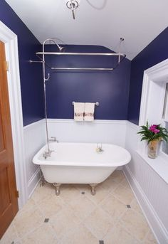 Small and narrow bathroom with a very small and elegant tub that doubles as a sower unit