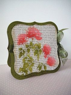 By Donna Mikasa. Stamp background text with a soft ink. For the flower, use a stamp with a lot of negative space. Ink with VersaMark & stamp onto background. Emboss in clear. Sponge bundled sage onto leaf areas and light pink onto flower areas. Then add some darker pinks to parts of the flowers and peeled paint to parts of the leaves. With wet paintbrush, blend the pink inks & then the green inks. Cut mat to size & attach to card base. Add embellishments & sentiment.