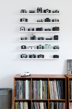 This image was really cool, I loved the clean cut layout of this image. How the shelves of the camera's are set so perfectly in the centre of the white wall, the desk/cupboard at the bottom adds an element to the image that makes it more interesting. The collection of camera's have been laid out so beautifully and perfectly spaced, the gap on the second shelf leads the viewer to wonder: is that camera being used to take the photograph? - KW…