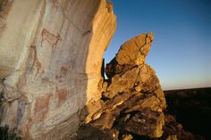 Finger paintings in red of eland and giraffe, and positive handprints, with setting sun lighting right-hand side. #africanrockart http://africanrockart.org